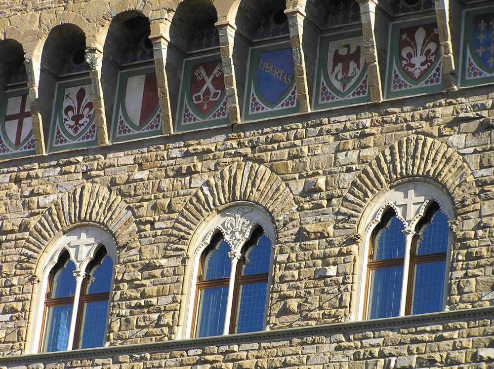 Detalle de las ventanas y escudos de armas de Palazzo Vecchio, Florencia, Italia. Autor y Copyright Marco Ramerini