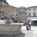 Une fontaine et en arrière-plan la tour ronde des murs de la ville, Cetona, Sienne. Auteur et Copyright Marco Ramerini