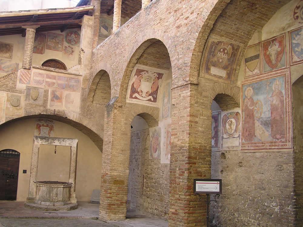Fresken in den Hof des Palazzo del Popolo, Piazza del Duomo, San Gimignano, Siena. Autor und Copyright Marco Ramerini